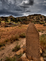 A headstone forms the foreground for a ruined Spanish Mission in the Purgatoire River valley.